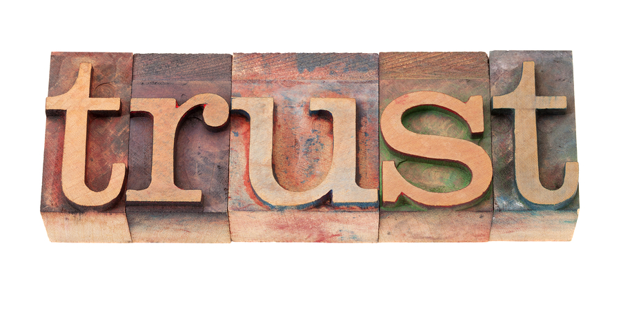 trust word in vintage wooden letterpress printing blocks stained by color inks isolated on white